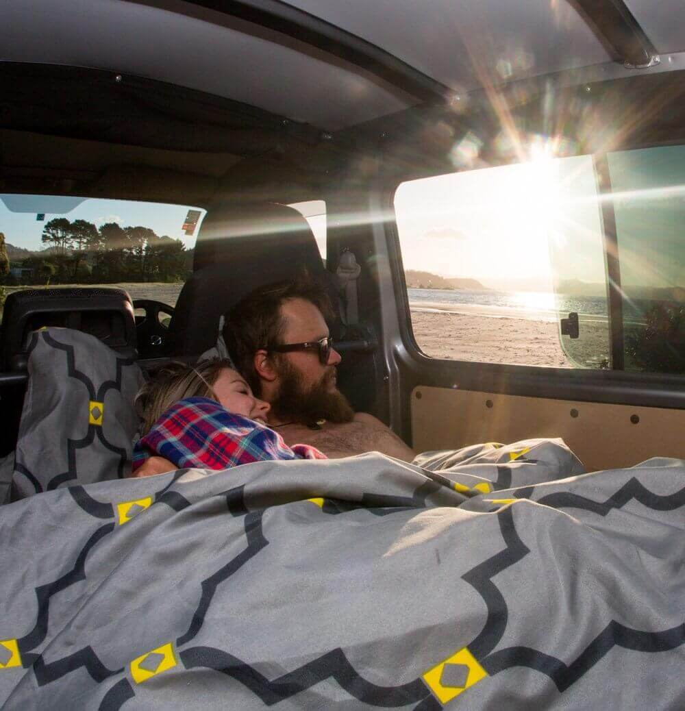 Queen size bed inside a campervan