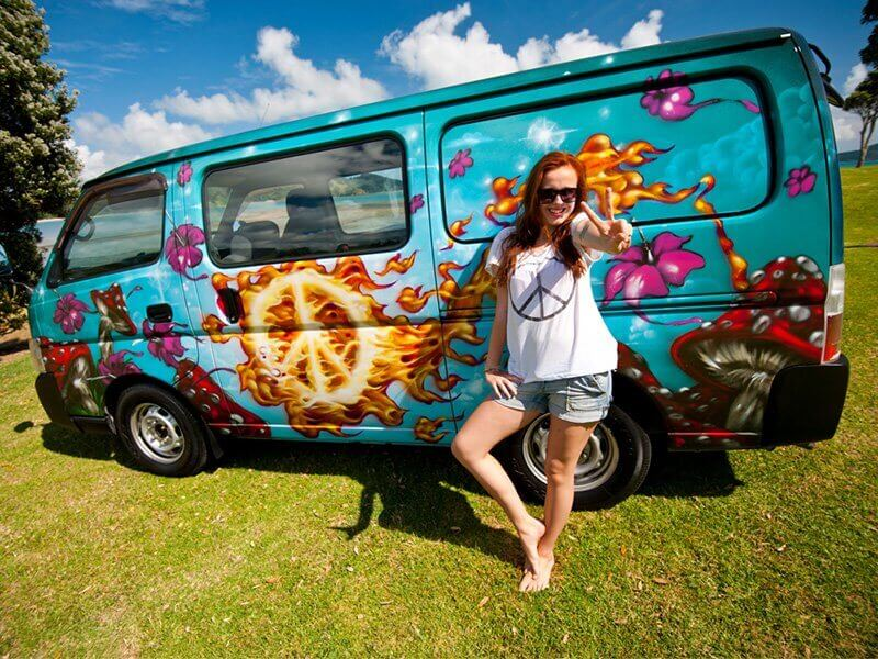 Girl posing for a photo with a campervan